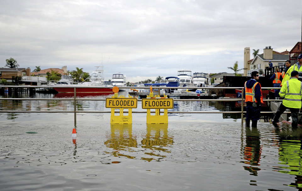 Officials stand near a flooded marina Wednesday morning, Dec. 13, 2012 in the Sunset Beach area of Huntington Beach, Calif. Astronomical high tides have caused minor street flooding in some low-lying areas along the Southern California coast. (AP Photo/The Daily Breeze, Sean Hiller)  MAGS OUT; NO SALES