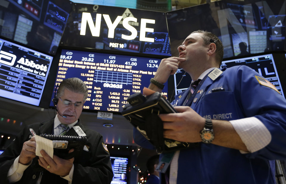 Daniel Kryger, left, and Kevin Lodewick Jr., right, follow trading from the floor of the New York Stock Exchange in New York, Wednesday, Dec. 27, 2012. (AP Photo/Kathy Willens)