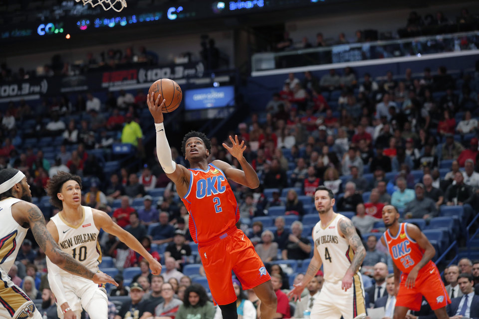 Photo - Oklahoma City Thunder guard Shai Gilgeous-Alexander (2) goes to the basket between New Orleans Pelicans center Jaxson Hayes (10) and guard JJ Redick (4) in the first half of an NBA basketball game in New Orleans, Sunday, Dec. 1, 2019. (AP Photo/Gerald Herbert)
