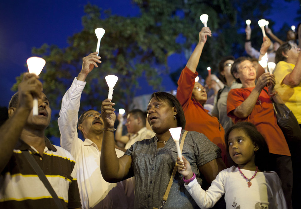 Photo - People hold up candles during candlelight vigil for Venezuela's President Hugo Chavez to pray for his health as he remains in a hospital undergoing cancer treatment, in Caracas, Venezuela, Friday, Feb. 22, 2013. Chavez hasn't spoken publicly since before he underwent his latest cancer surgery on Dec. 11. (AP Photo/Ariana Cubillos)