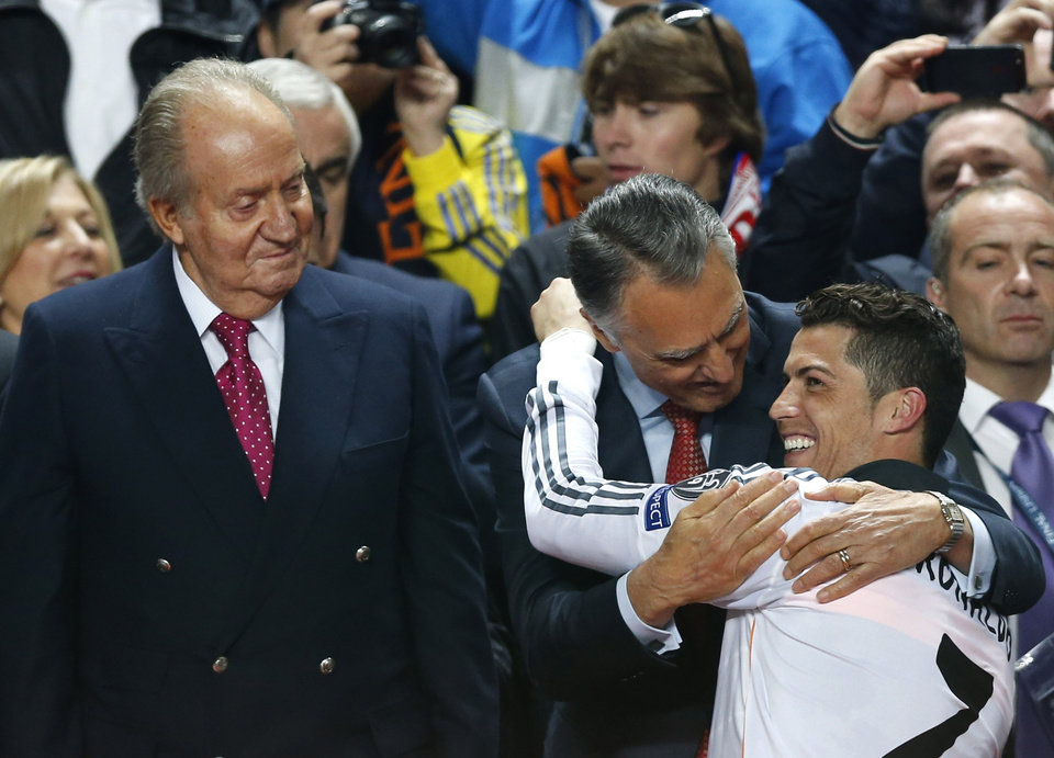 Photo - Portugal's President Anibal Cavaco Silva embraces Real's Cristiano Ronaldo next to Spanish king Juan Carlos after the end of the Champions League final soccer match between Atletico de Madrid and Real Madrid in Lisbon, Portugal, Saturday, May 24, 2014. Real Madrid won 4-1. (AP Photo/Daniel Ochoa de Olza)