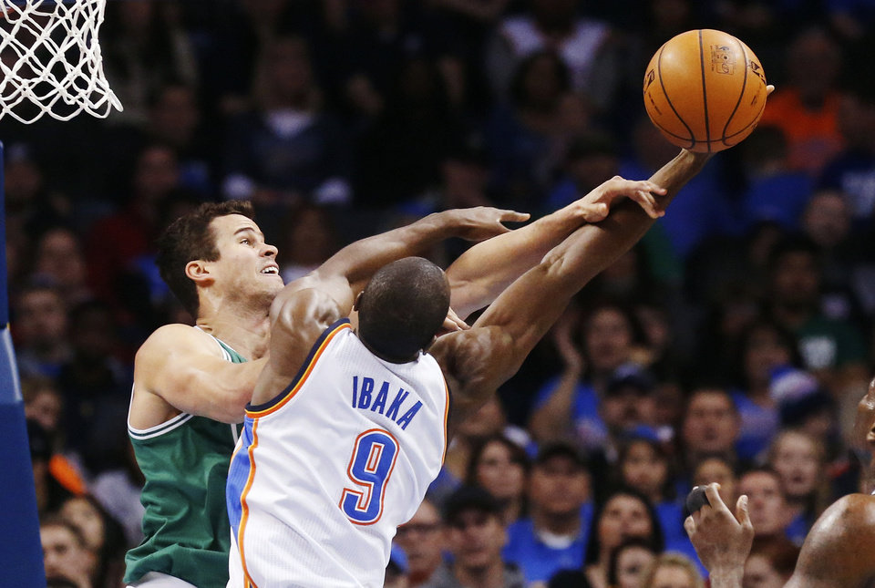 Photo - Boston Celtics forward Kris Humphries, left, and Oklahoma City Thunder forward Serge Ibaka (9) reach for a rebound in the first quarter of an NBA basketball game in Oklahoma City, Sunday, Jan. 5, 2014. (AP Photo/Sue Ogrocki)