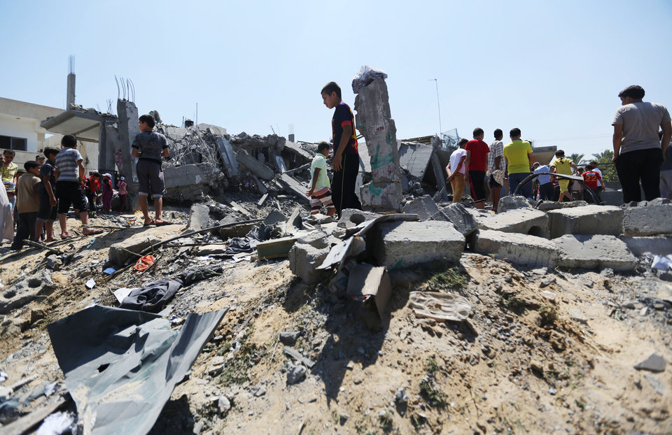 Photo - Palestinians inspect the rubble of a house after it was hit by an Israeli missile strike in Khan Younis, southern Gaza Strip, Tuesday, July 8, 2014. The Israeli military launched what could be a long-term offensive against the Hamas-ruled Gaza Strip on Tuesday striking at least 50 sites in Gaza by air and sea and mobilizing troops for a possible ground invasion aimed at stopping a recent barrage of rocket attacks against Israel. (AP Photo/Hatem Moussa)