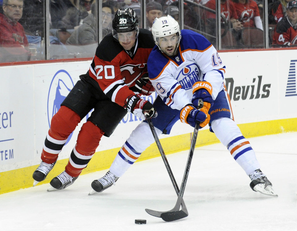 Photo - New Jersey Devils' Ryan Carter, left, battles for control of the puck with Edmonton Oilers' Justin Schultz during the second period of an NHL hockey game, Friday, Feb. 7, 2014, in Newark, N.J. (AP Photo/Bill Kostroun)
