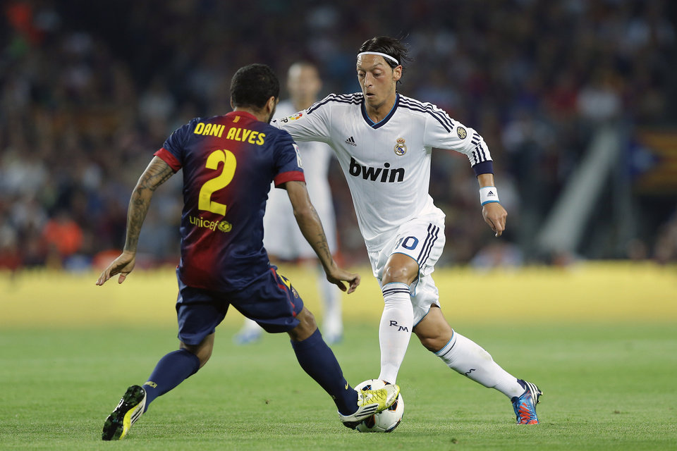 Barcelona\'s Daniel Alves from Brazil, left, duels for the ball with Real Madrid\'s Mesut Ozil from Germany during a Spanish La Liga soccer match at the Camp Nou Stadium, in Barcelona, Spain, Sunday, Oct. 7, 2012. (AP Photo/Daniel Ochoa De Olza)