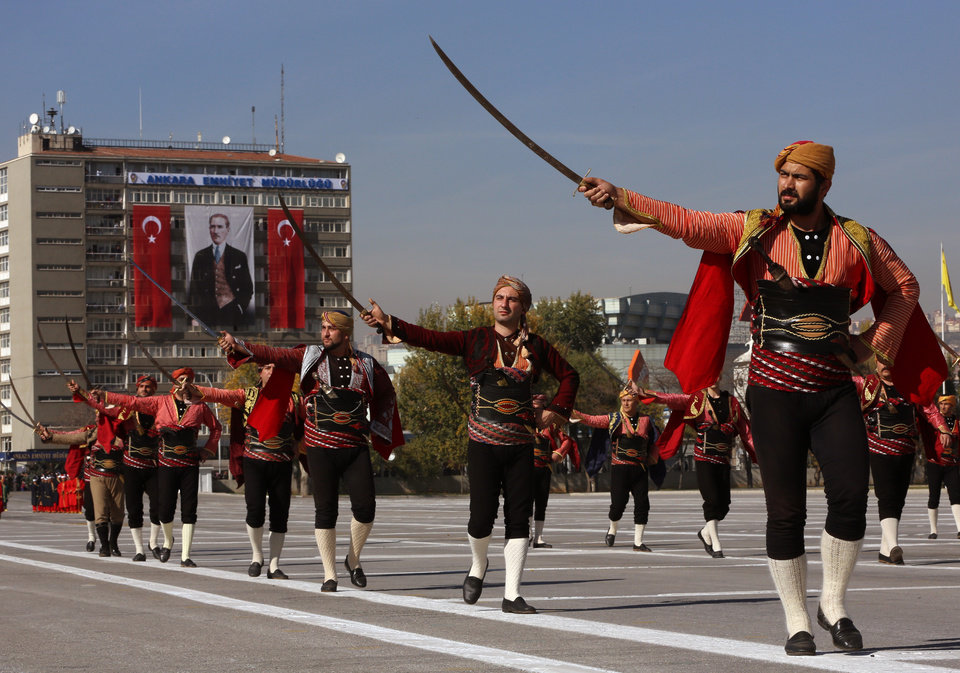 Photo - The Seymens, representing Ankara local militia who welcomed Mustafa Kemal Atuturk in Ankara in 1919 as Atuturk arrived to organize the the Independence war that led to the foundation of Turkish republic, march during the celebrations for the 90th anniversary of  republic in Ankara, Turkey, Tuesday, Oct. 29, 2013. A poster of Atuturk hangs from a building in the background.(AP Photo/Burhan Ozbilici)