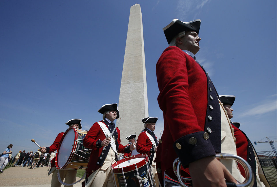 Photo - Members of the United States Army Old Guard Fife and Drums Corps march beneath the Washington Monument in Washington, Monday, May 12, 2014, during a ceremony to celebrate its re-opening. The monument, which sustained damage from an earthquake in August 2011, reopened to the public today. (AP Photo)