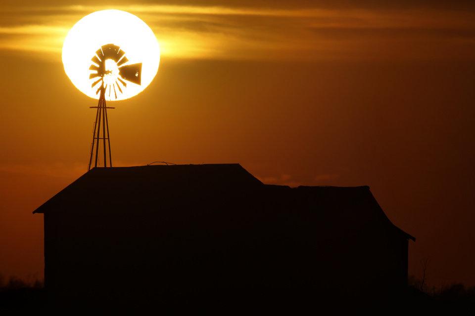 SUNSET: The sun sets behind a windmill near Piedmont Road and the Northwest Expressway in Piedmont , Tuesday April 30 2013. Photo By Steve Gooch, The Oklahoman