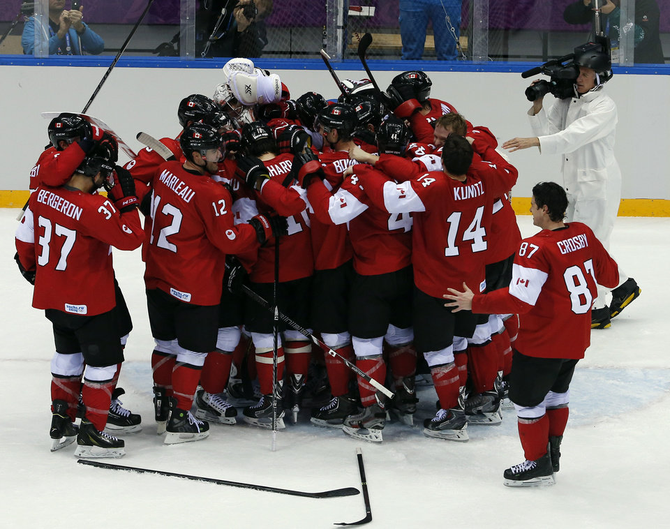 Photo - Canada forward Sidney Crosby goes to join his teammates as they celebrate after the men's gold medal ice hockey game against Sweden at the 2014 Winter Olympics, Sunday, Feb. 23, 2014, in Sochi, Russia. Canada won 3-0 to win the gold medal. (AP Photo/David J. Phillip )