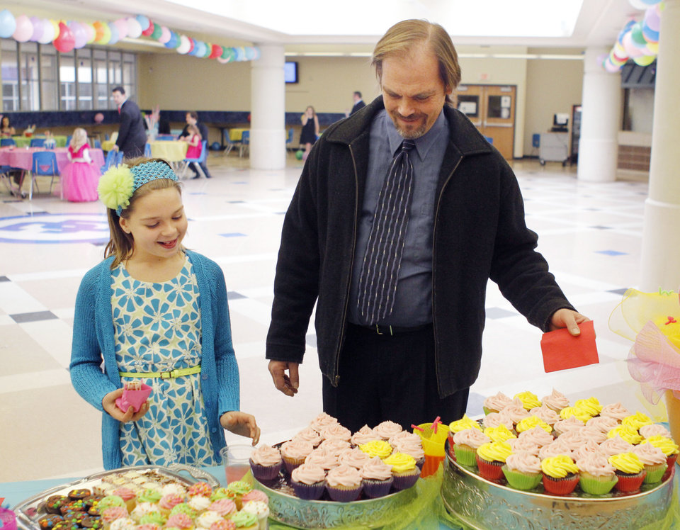 Dave Fedder and his daughter Indianna pick up some cupcakes during the Deer Creek Daddy daughter dance at Deer Creek High School in Oklahoma City, OK, Saturday, January 26, 2013,  By Paul Hellstern, The Oklahoman
