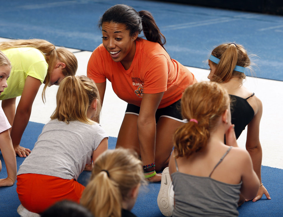 Photo - Instructor Whittney Coby talks with participants at the cheer and tumbling camp.