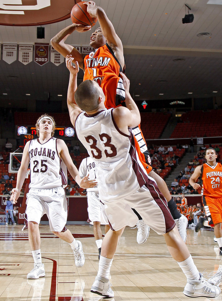 Photo - Putnam City's Tre Payne goes over Jenks' C.J. Sidorakis as Brian Brookey watches during the Class 6A boys championship game between Putnam City and Jenks in the Oklahoma High School Basketball Championships at Lloyd Noble Arena in Norman, Okla., Saturday, March 14, 2009. PHOTO BY BRYAN TERRY, THE OKLAHOMAN