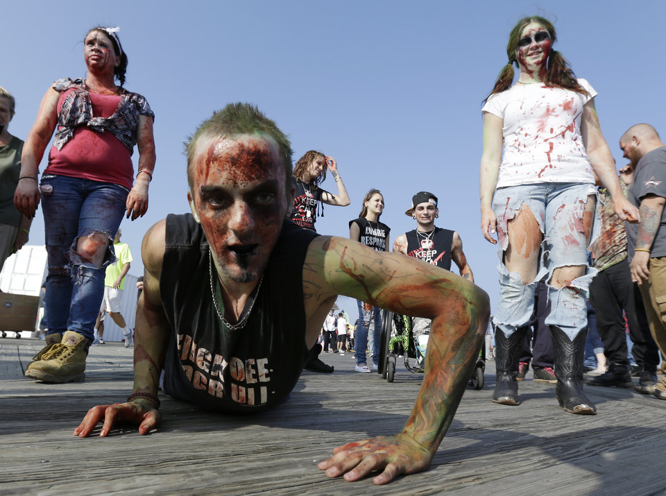 Photo - Joe Wiley, of Hamilton, N.J., crawls on the Asbury Park boardwalk during a zombie walk, Saturday, Oct. 5, 2013, in Asbury Park, N.J. According to Guinness World Record adjudicator Michael Empric, the 9,592 zombies gathered sets a new record for largest zombie walk. (AP Photo/Julio Cortez) ORG XMIT: NJJC107
