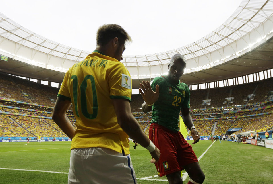 Photo - Cameroon's Allan Nyom tries to shake hands with Brazil's Neymar after pushing him to the ground in the corner during the group A World Cup soccer match between Cameroon and Brazil at the Estadio Nacional in Brasilia, Brazil, Monday, June 23, 2014. (AP Photo/Natacha Pisarenko)