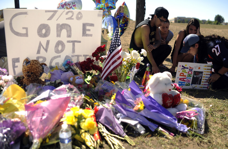 Photo -   Friends of shooting victim Alex Sullivan sign the 27th birthday card of Sullivan at memorial of shooting victims near the movie theater in Aurora, Colo. on Saturday, July 21, 2012. Twelve people were killed and dozens were injured in the attack early Friday at the packed theater during a showing of the Batman movie,