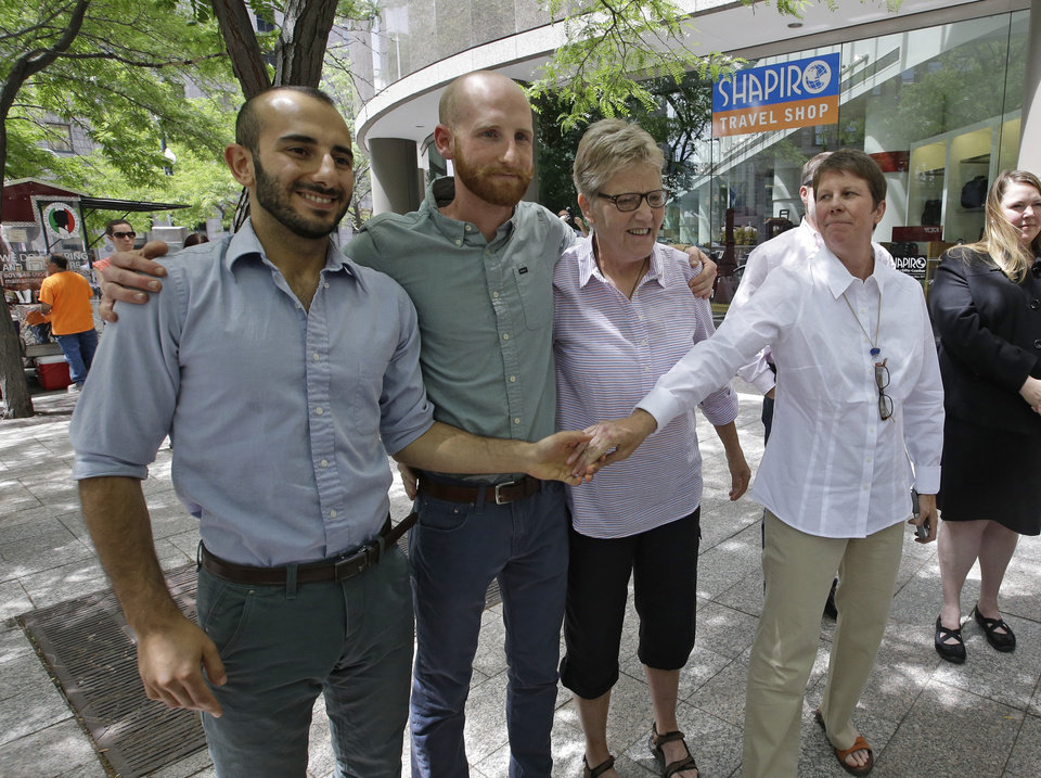 Photo - From left, plaintiffs Moudi Sbeity, Derek Kitchen, Laurie Wood and Kody Partridge, two of the three couples who brought the lawsuit against Utah's gay marriage ban, stand together at a news conference outside their lawyer's office in Salt Lake City on Wednesday, June 25, 2014. Earlier in the day, a federal appeals court ruled that states must allow gay couples to marry, finding the Constitution protects same-sex relationships. The decision from a three-judge panel in Denver upheld a lower court ruling that struck down Utah's gay marriage ban. (AP Photo/Rick Bowmer)