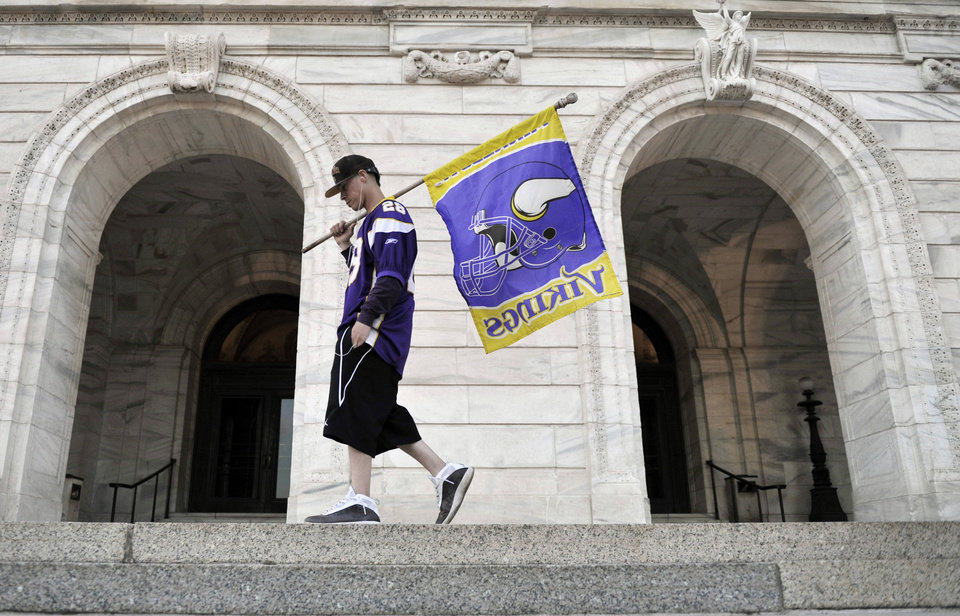 Minnesota Vikings fan George Green of St. Paul, Minn., walks with a team flag in front of the State Capitol in the early evening as lawmakers in the Minnesota House were taking up a bill for a new stadium for the Vikings NFL football team Monday, May 7, 2012, in St. Paul. (AP Photo/Jim Mone)