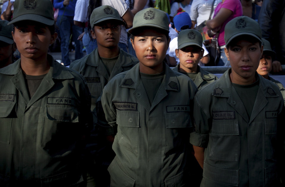 Photo - Women soldiers wait for the the arrival of Venezuela's President Nicolas Maduro in Bolivar Square for a rally to commemorate International Women's Day in Caracas, Venezuela, Saturday, March 8, 2014. (AP Photo/Alejandro Cegarra)