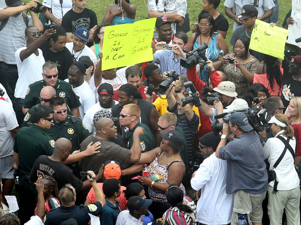 Photo - Deputies try to maintain calm after demonstrators become involved in a shouting match outside the Seminole County Criminal Justice Center during jury deliberations in the trial of George Zimmerman , in Sanford, Fla., Saturday, July  13, 2013. Zimmerman has been charged with the 2012 shooting death of Trayvon Martin.(AP Photo/Orlando Sentinel, Joe Burbank, Pool) ORG XMIT: FLJR225