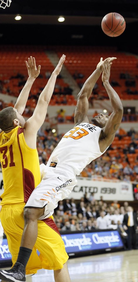 Photo - Oklahoma State Cowboys' Marcus Smart (33) puts up a shot over Iowa State Cyclones' Georges Niang (31) during the college basketball game between the Oklahoma State University Cowboys (OSU) and the Iowa State University Cyclones (ISU) at Gallagher-Iba Arena on Wednesday, Jan. 30, 2013, in Stillwater, Okla.  Photo by Chris Landsberger, The Oklahoman