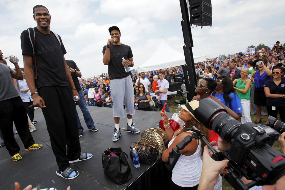 Photo - Kevin Durant, left, smiles as Russell Westbrook speaks to fans during a welcome home rally for the Oklahoma City Thunder in a field at Will Rogers World Airport after the team's loss to the Miami Heat in the NBA Finals, Friday, June 22, 2012. Photo by Nate Billings, The Oklahoman