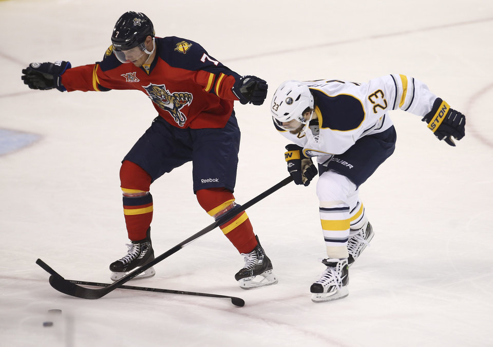 Photo - Florida Panthers' Dmitry Kulikov (7) reacts after he broke his stick while he and Buffalo Sabres' Ville Leino (23) chase the puck during the second period of an NHL hockey game in Sunrise, Fla., Friday, March 7, 2014. (AP Photo/J Pat Carter)