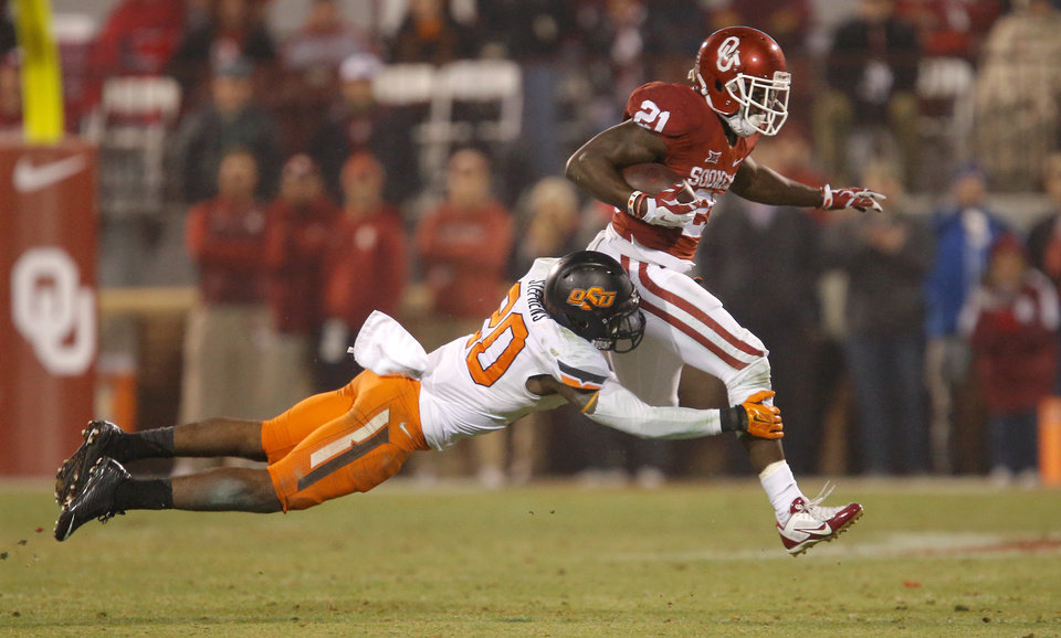Photo - Oklahoma's Keith Ford (21) is brought down by Oklahoma State's Larry Stephens (20) on the last play of regulation during a Bedlam college football game between the University of Oklahoma Sooners (OU) and the Oklahoma State Cowboys (OSU) at Gaylord Family-Oklahoma Memorial Stadium in Norman, Okla., Saturday, Dec. 6, 2014. Photo by Bryan Terry, The Oklahoman
