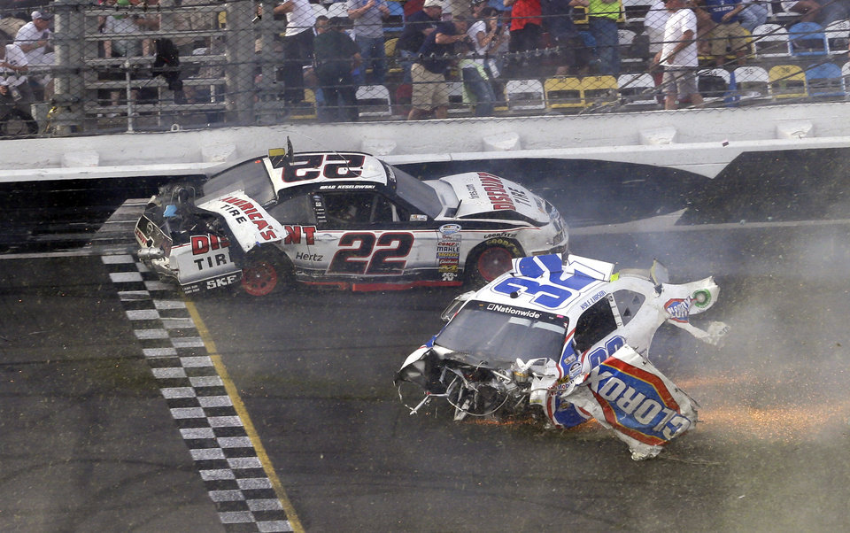 Brad Keselowski (22) and Kyle Larson (32) slide across the finish line after they were involved in a mulit-car crash on the final lap of the NASCAR Nationwide Series auto race at Daytona International Speedway, Saturday, Feb. 23, 2013, in Daytona Beach, Fla. (AP Photo/John Raoux)
