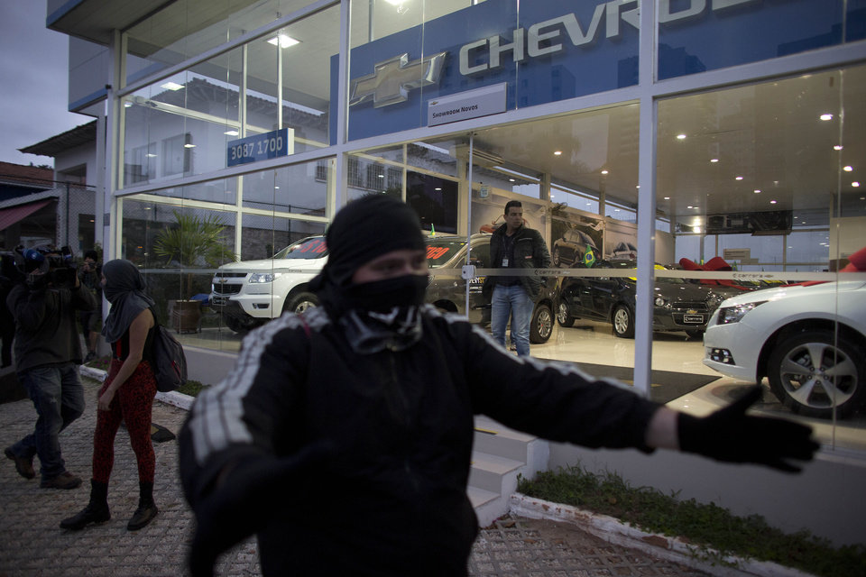 Photo - A masked protester tries to keep others from vandalizing a car dealership while marching  in Sao Paulo, Brazil, Thursday, June 19, 2014.  The protest in Sao Paulo, Brazil's biggest city that is hosting a World Cup match,  was called by the Free Fare movement, the group that was behind the first protests last year that sparked roiling anti-government demonstrations across Brazil.  (AP Photo/Dario Lopez-Mills)