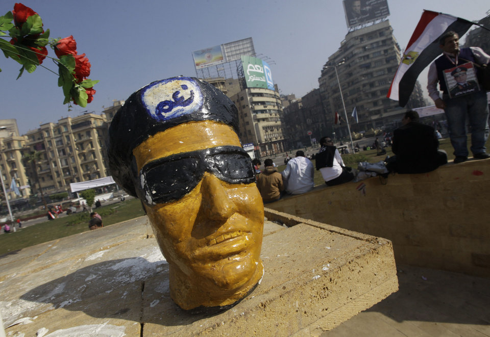 Photo - A figurine representing Egypt's Defense Minister Gen. Abdel-Fattah el-Sissi sits at the memorial in Tahrir Square, the epicenter of the 2011 uprising, in Cairo, Egypt, Saturday, Jan. 25, 2014. Demonstrators began gathering Saturday in Egypt's Tahrir Square to mark the third anniversary of the start of its 2011 revolution, following a spate of bombings claimed by militants. The Arabic on the statuette reads,