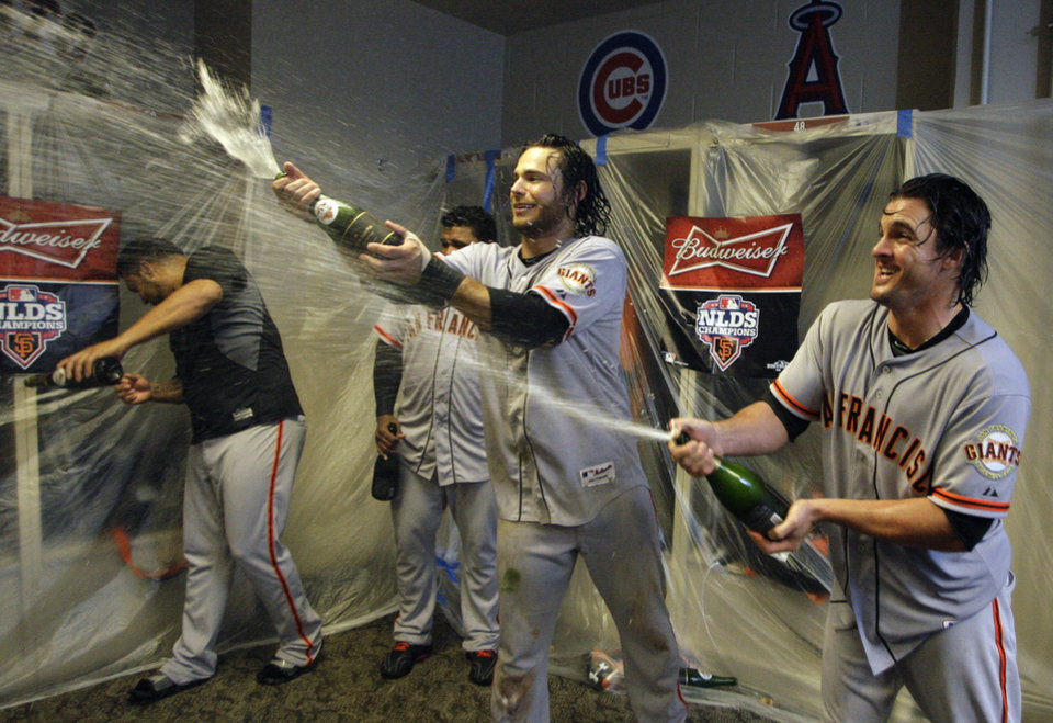 Photo -   San Francisco Giants' Brandon Crawford, center, and Ryan Theriot, right, spray champagne in the locker room after they defeated the Cincinnati Reds 6-4 in Game 5 of the National League division baseball series, Thursday, Oct. 11, 2012, in Cincinnati. The Giants won the final three games, all in Cincinnati, and advanced to the NL championship series. (AP Photo/David Kohl)