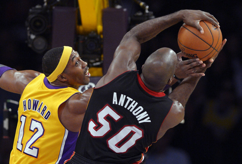 Photo - Los Angeles Lakers center Dwight Howard (12) reaches for a rebound with Miami Heat center Joel Anthony during the first half of their NBA basketball game, Thursday, Jan. 17, 2013, in Los Angeles. (AP Photo/Mark J. Terrill)