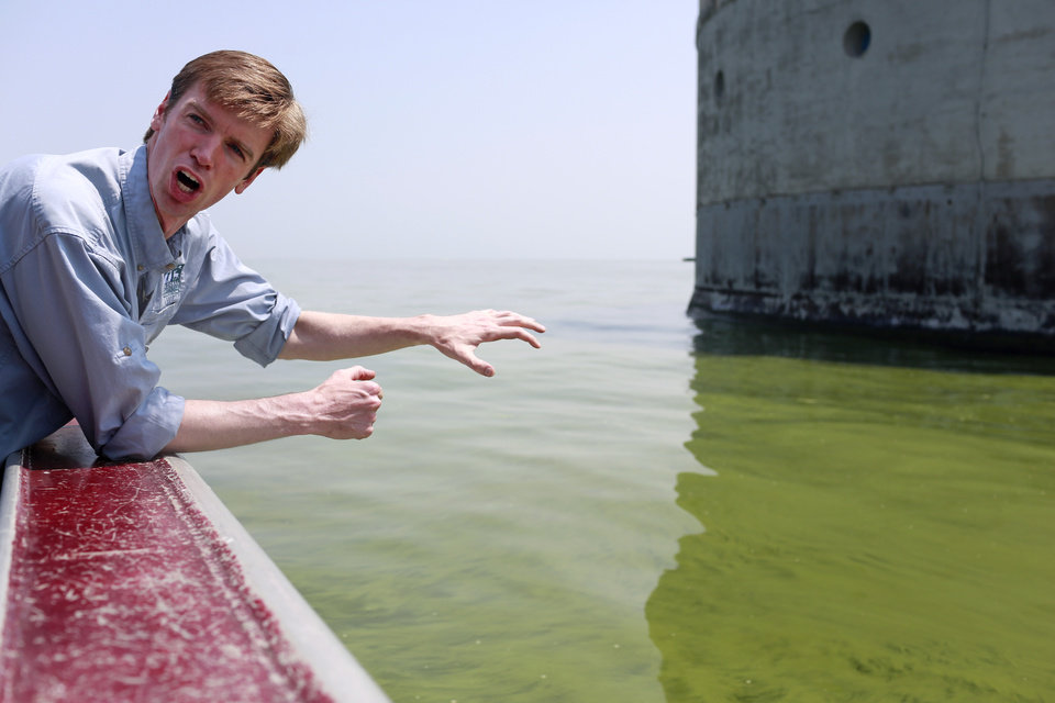 Photo - Collin O'Mara, president and CEO of the National Wildlife Federation, gestures as he talks about algae near the City of Toledo water intake crib, Sunday, Aug. 3, 2014, in Lake Erie, about 2.5 miles off the shore of Curtice, Ohio. More tests are needed to ensure that toxins are out of Toledo's water supply, the mayor said Sunday, instructing the 400,000 people in the region to avoid drinking tap water for a second day. Toledo officials issued the warning early Saturday after tests at one treatment plant showed two sample readings for microcystin above the standard for consumption, possibly because of algae on Lake Erie. (AP Photo/Haraz N. Ghanbari)