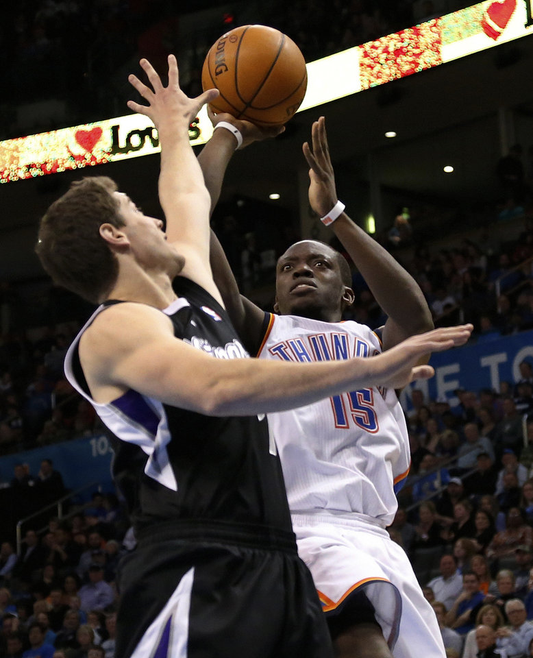 Photo - Oklahoma City Thunder guard Reggie Jackson (15) shoots as Sacramento Kings guard Jimmer Fredette (7) defends in the fourth quarter of an NBA basketball game in Oklahoma City, Sunday, Jan. 19, 2014. Oklahoma City won 108-93. (AP Photo/Sue Ogrocki)