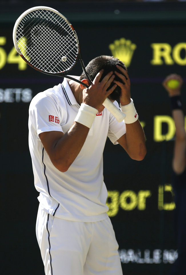Photo - Novak Djokovic of Serbia puts his hands on his head during the men's singles semifinal match against  Grigor Dimitrov of Bulgaria at the All England Lawn Tennis Championships in Wimbledon, London, Friday, July 4, 2014. (AP Photo/Pavel Golovkin)