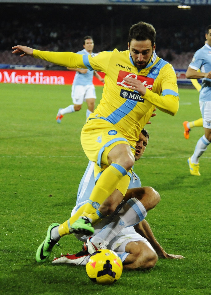 Photo - Napoli's Gonzalo Higuaín is tackled by Lazio's Diego Novaretti during an Italian Cup Cup quarterfinal soccer match between Napoli and Lazio, at the San Paolo stadium in Naples, Italy, Wednesday, Jan. 29, 2014. (AP Photo/Salvatore Laporta)