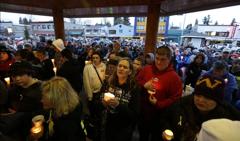 Photo - People gather Tuesday, March 25, 2014, at a candlelight vigil in Arlington, Wash., for the victims of a massive mudslide that struck the nearby community of Oso, Wash., on Saturday, killing at least 16 people and leaving dozens missing. (AP Photo/Ted S. Warren)