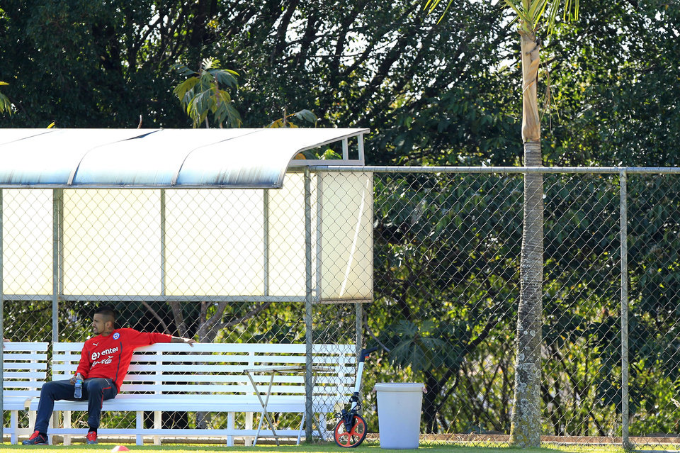 Photo - Chile's Arturo Vidal sits on a bench during a training session at Toca da Raposa 2, in Belo Horizonte, Brazil, Monday, June 9, 2014. Vidal, who is recovering from an injury, did not train. Chile will play in group B of the Brazil 2014 World Cup. (AP Photo/Bruno Magalhaes)