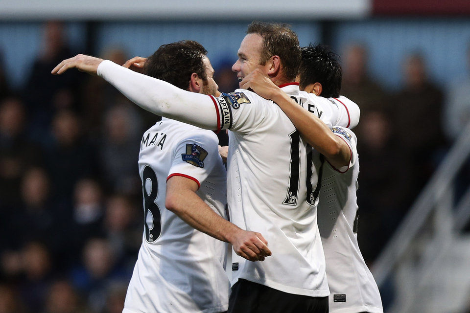 Photo - Manchester United's Wayne Rooney, center, celebrates his second goal against West Ham United with teammates during their English Premier League soccer match at Upton Park, London, Saturday, March 22, 2014. (AP Photo/Sang Tan)
