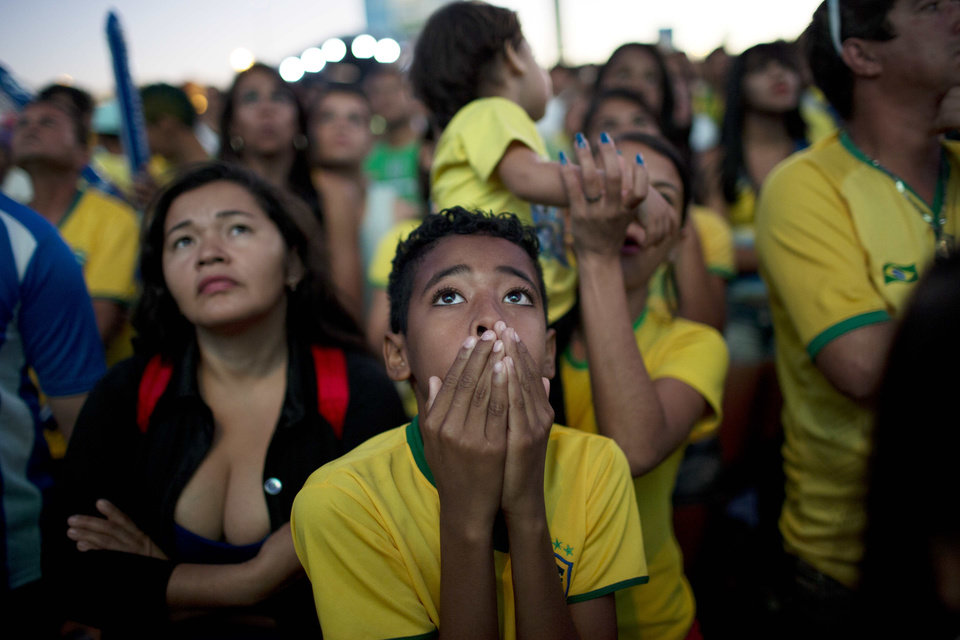 Photo - A Brazil soccer fan watches the World Cup quarterfinal match between Brazil and Colombia on a live telecast inside the FIFA Fan Fest area in Taquatinga, Brazil, Friday, July 4, 2014. Brazil won 2-1. (AP Photo/Rodrigo Abd)