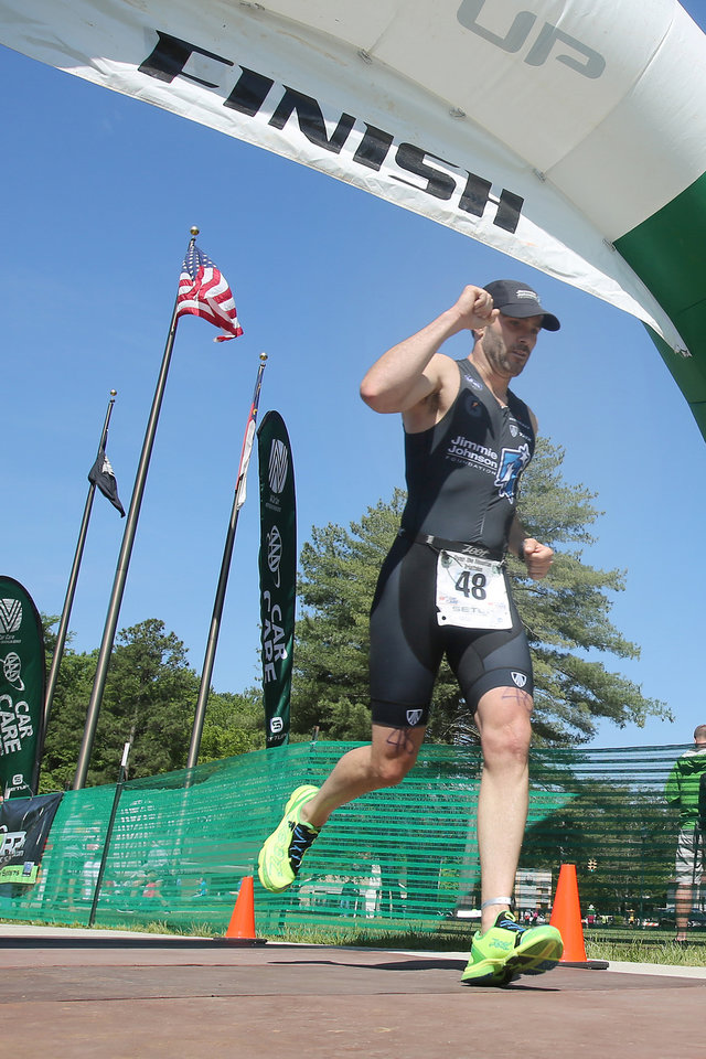 Photo - Six-time NASCAR champion driver Jimmie Johnson finishes the Over the Mountain Triathlon in Kings Mountain, N.C., Saturday, May 17, 2014.  (AP Photo/The Star, Ben Earp)