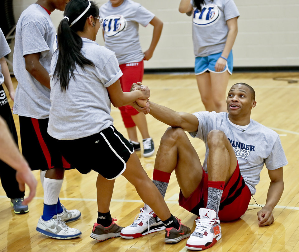 Russell Westbrook gets some help to get off the court from Nina Kopaddy during a visit by the Oklahoma City Thunder to students at U.S. Grant High School to promote physical fitness on Monday, Jan. 28, 2013, in Oklahoma City, Okla.  Photo by Chris Landsberger, The Oklahoman