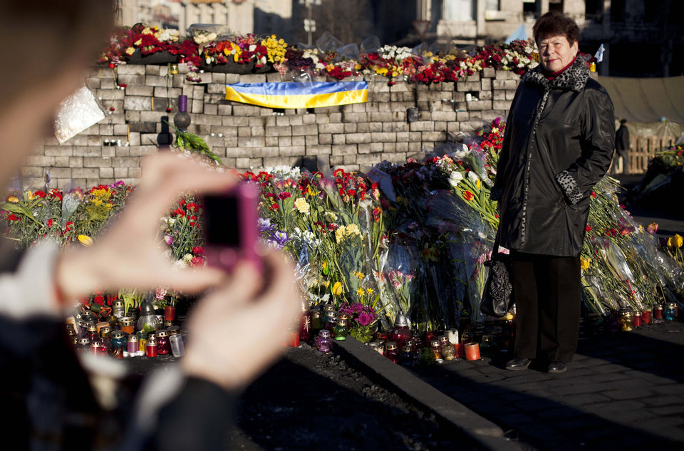 Photo - A woman poses for a photograph next to a wall composed of paving stones and adorned with flowers and candles placed in memory of those who died in clashes which took place in late February in Kiev's Independence Square, Ukraine, Tuesday, March 11, 2014. (AP Photo/David Azia)