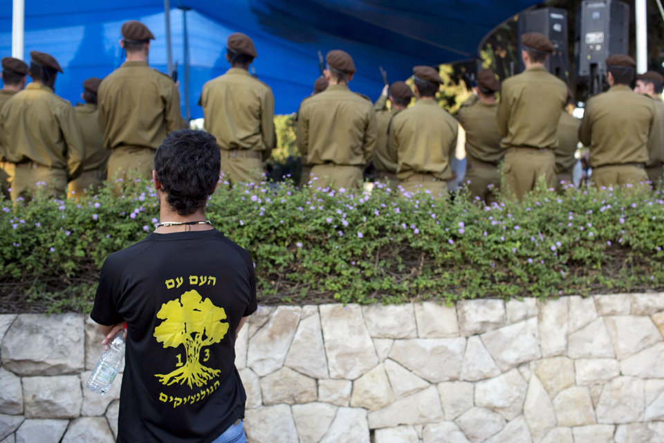 Photo - An Israeli man wears a T-shirt with the Golani brigade unit symbol during the funeral of Sgt. Sean Mondshane, at a cemetery in Tel Aviv, Israeli, Tuesday, July 22, 2014. Mondshane, who served in the Golani brigade, was killed in fighting in the Gaza Strip on Sunday. (AP Photo/Oded Balilty)