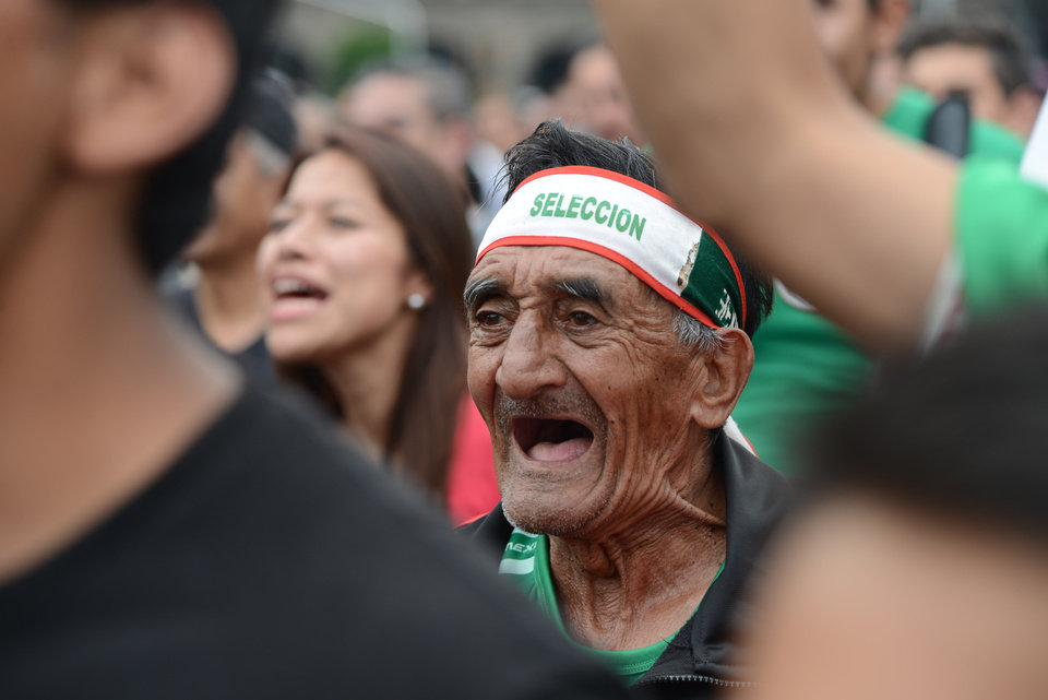 Photo - A Mexico soccer fan cheers while watching his team play Brazil in the World Cup on a large screen set up at the Zocalo in Mexico City, Tuesday June 17, 2014. Mexico claimed a deserved point against Brazil in a largely frustrating Group A game which finished 0-0 at Estadio Castelao in Fortaleza. (AP Photo/Sean Havey)