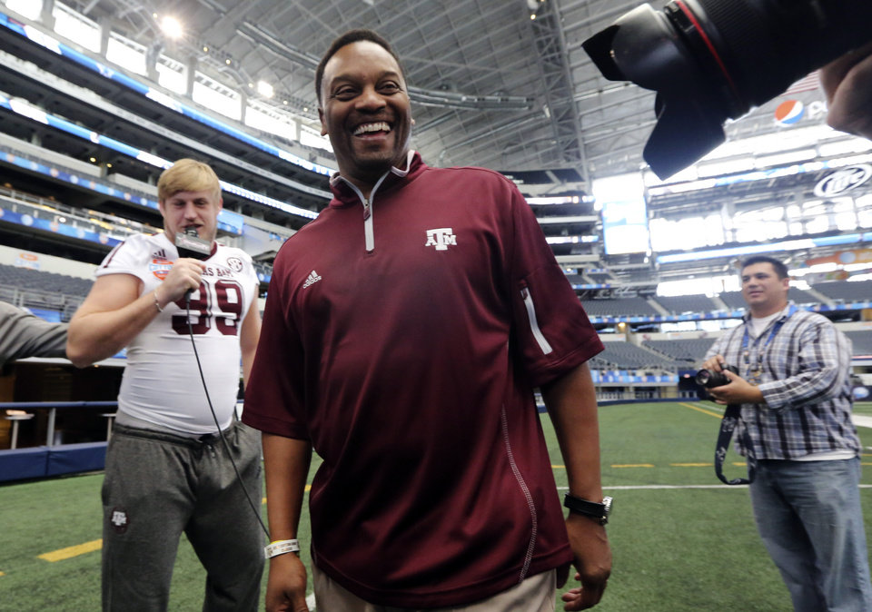 Photo - Texas A&M head coach Kevin Sumlin laughs after defensive lineman Spencer Nealy tried to interview him during media day for the Cotton Bowl NCAA college football game at Cowboys Stadium, Sunday, Dec. 30, 2012, in Arlington, Texas. Texas A&M is scheduled to play Oklahoma on Jan. 4, 2013. (AP Photo/LM Otero) ORG XMIT: TXMO111