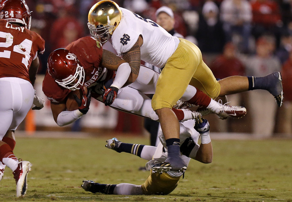 OU\'s Trey Millard (33) is bought down by Notre Dame\'s Manti Te\'o (5) during the college football game between the University of Oklahoma Sooners (OU) and the Notre Dame Fighting Irish at Gaylord Family-Oklahoma Memorial Stadium in Norman, Okla., Saturday, Oct. 27, 2012. Photo by Bryan Terry, The Oklahoman