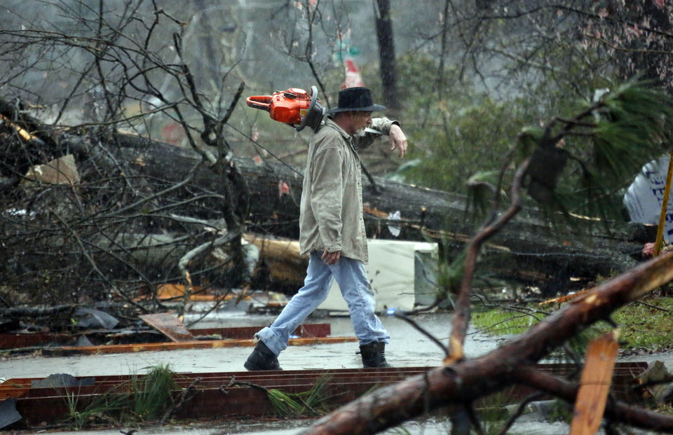 Photo - A Hattiesburg, Miss., resident walks through a tornado damaged neighborhood Monday, Feb. 11, 2013, after cutting away branches blocking a senior citizen's entrance to her home following a Sunday afternoon tornado that caused damage throughout the South Mississippi college town. (AP Photo/Rogelio V. Solis)