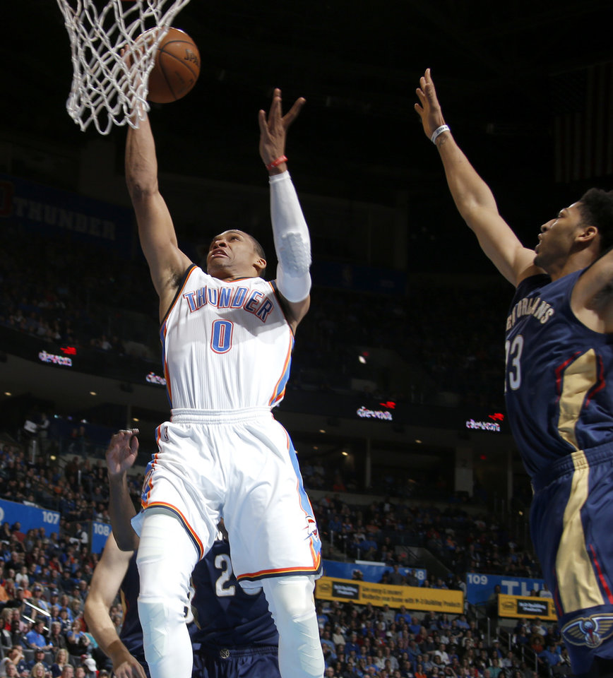 Photo - Oklahoma City's Russell Westbrook (0) god past New Orleans' Anthony Davis (23) during an NBA game between the Oklahoma City Thunder and the New Orleans Pelicans at Chesapeake Energy Arena on Friday, Feb. 6, 2015. Photo by Bryan Terry, The Oklahoman