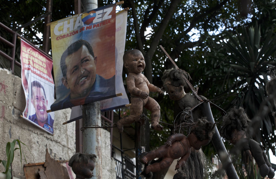 Election campaign posters of President Hugo Chavez hang by dolls on display outside the doll collector's home in downtown Caracas, Venezuela, Saturday, Oct. 6, 2012. Chavez is running for re-election against opposition leader Henrique Capriles in Sunday's presidential election. (AP Photo/Ramon Espinosa)